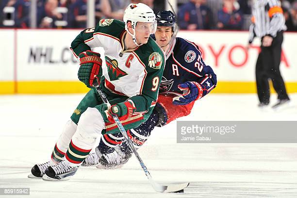 Mikko Koivu of the Minnesotta Wild skates the puck away from Manny Malhotra of the Columbus Blue Jackets during the third period on April 11, 2009 at...