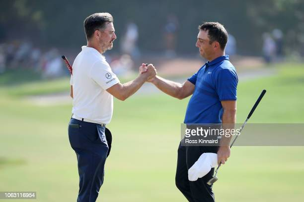 Mikko Korhonen of Finland and Francesco Molinari of Italy shake hands after finishing on the 18th hole during day four of the DP World Tour...