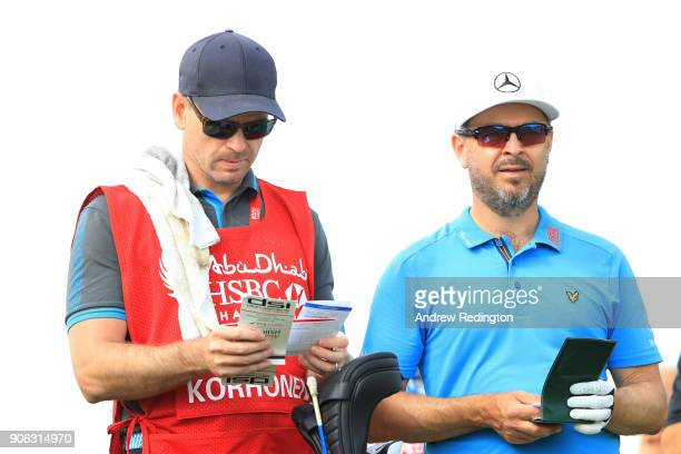 Mikko Korhonen of Finland talks with his caddie on the 14th tee during round one of the Abu Dhabi HSBC Golf Championship at Abu Dhabi Golf Club on...