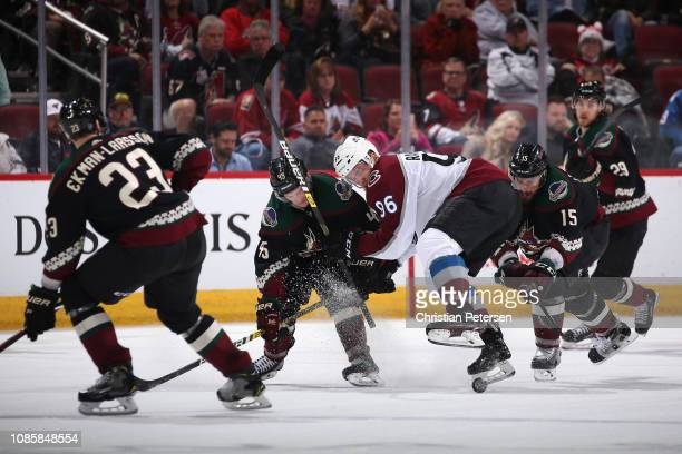 Mikko Rantanen of the Colorado Avalanche attempts to control the puck ahead of Josh Archibald and Brad Richardson of the Arizona Coyotes during the...