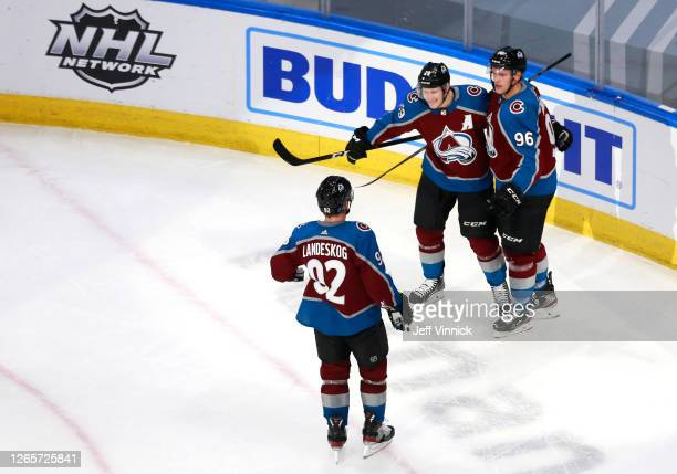 Mikko Rantanen of the Colorado Avalanche celebrates with Nathan MacKinnon and Gabriel Landeskog after scoring a goal on Darcy Kuemper of the Arizona...