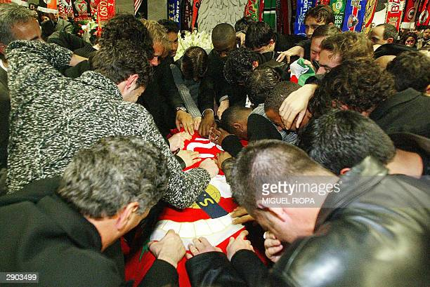 Miklos Feher Benfica's teammates embrace the coffin with the body of the Hungarian player in the Luz Stadium at Lisbon 26 January 2004 who died on...