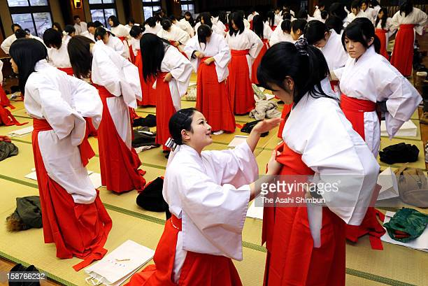 A Miko shrine maiden instructs how to dress the costumes to part time shrine maidens in preparation for the New Year celebration at Dazaifu Tenmangu...