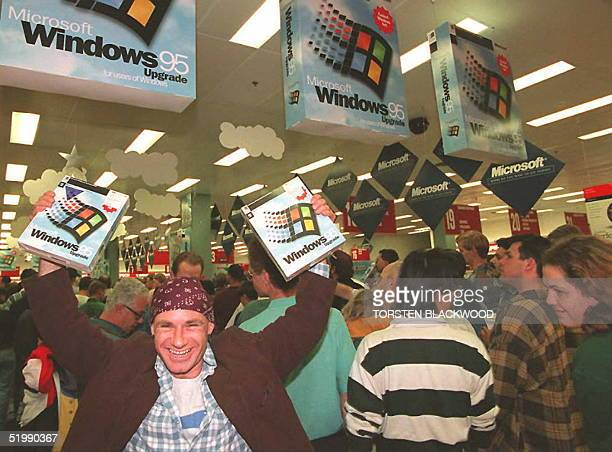 Mikol Furneaux waves two packages of Windows 95 software in the first store in Australia to sell the product at midnight 24 August Microsoft hopes to...