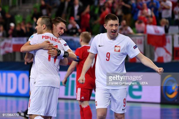Mikolaj Zastawnik Artur Poplawski and Tomasz Lutecki of Poland celebrate their victory during the UEFA Futsal EURO 2018 group B match between Russia...