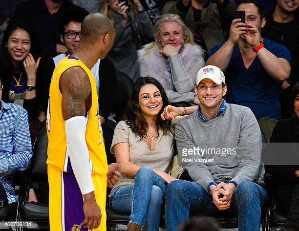 Mila Kunis and Ashton Kutcher talk at a basketball game between the Oklahoma City Thunder and the Los Angeles Lakers at Staples Center on December 19...
