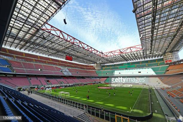 Milan and Genoa CFC players warm up in the empty stadium after rules to limit the spread of Covid-19 have been put in place before the Serie A match...
