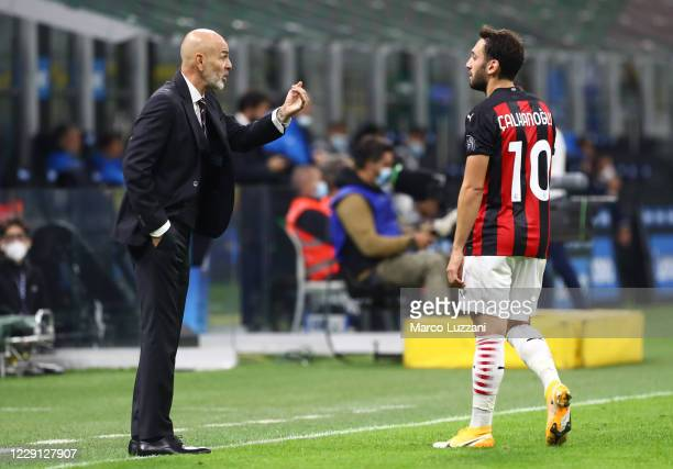 Milan coach Stefano Pioli issues instructions to his player Hakan Calhanoglu during the Serie A match between FC Internazionale and AC Milan at...