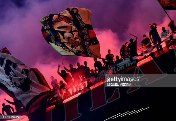Milan fans burn flare bombs and wave flags during the Italian Serie A football match AC Milan vs Inter Milan on September 21 2019 at the San Siro...