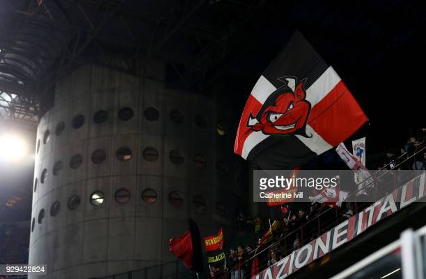 Milan fans waves flags inside the stadium during the UEFA Europa League Round of 16 match between AC Milan and Arsenal at the San Siro on March 8...