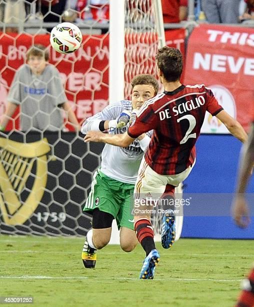 AC Milan goalkeeper Gabriel Vasconcellos makes a play on the ball as teammate Mattia De Sciglio closes in during the second half against Liverpool...