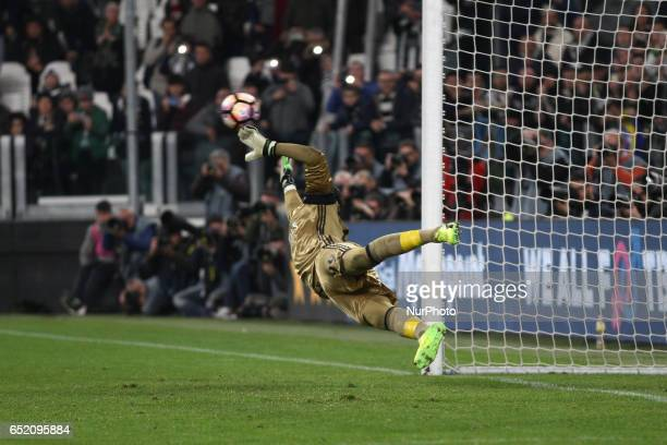 Milan goalkeeper Gianluigi Donnarumma dives for the ball shooter by Juventus forward Paulo Dybala on penalty kick during the Serie A football match...