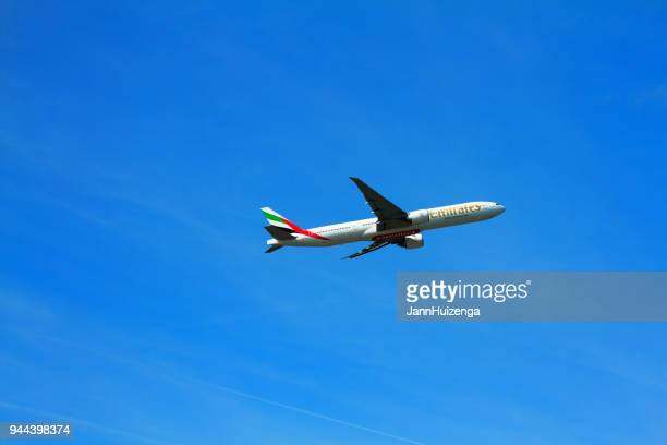 milan, italy: emirates airplane taking off in blue sky - emirates airline stock photos and pictures