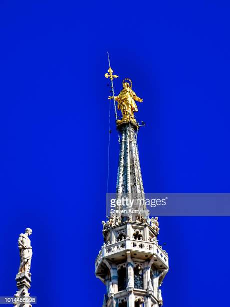 milan, italy, september 19, 2016: the golden statue of mother mary rises high above the milan cathedral (duomo) in milan, italy.  the statue is set against a dark blue sky. - piazza del duomo milano foto e immagini stock
