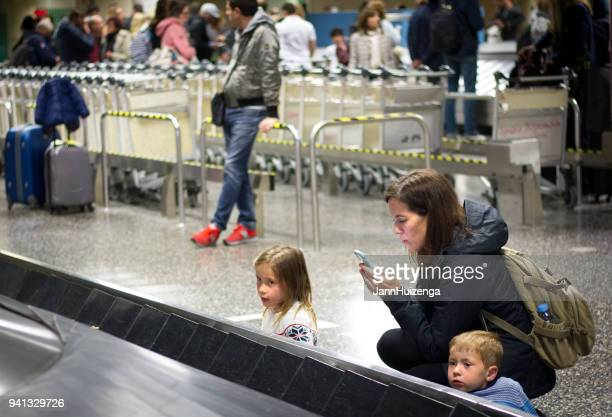 Milan, Italy: Woman (With Kids) Texting at Malpensa Airport