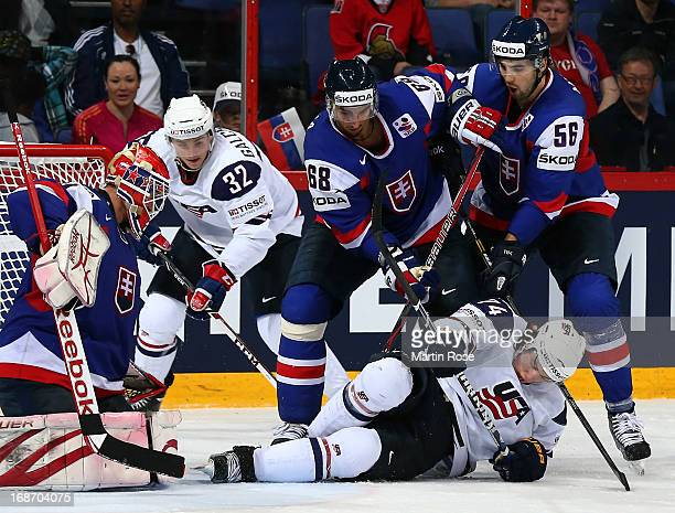 Milan Jurcina and Vladimir Mihalik of Slovakia and TJ Oshie of USA battle for the puck during the IIHF World Championship group H match between...