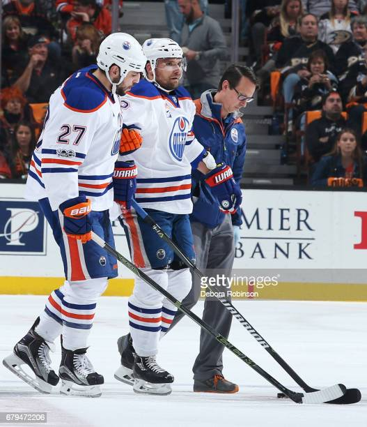 Milan Lucic and a trainer from the Edmonton Oilers help Andrej Sekera off the ice after getting injured in Game Five of the Western Conference Second...