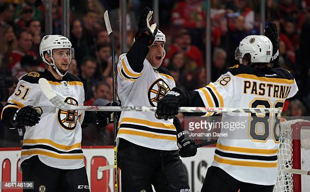Milan Lucic of the Boston Bruins celebrates a second period goal against the Chicago Blackhawks with teammates Ryan Spooner and David Pastrnak at the...