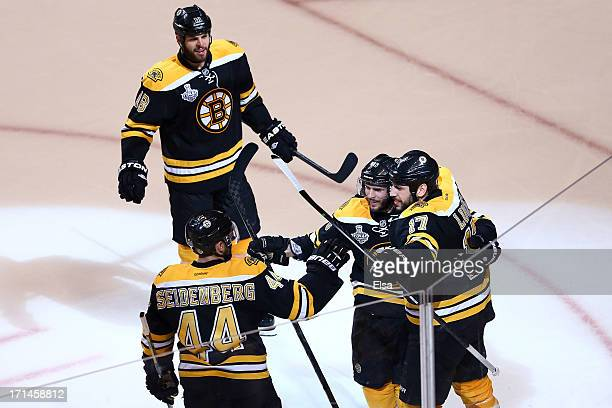 Milan Lucic of the Boston Bruins celebrates with his teammates Nathan Horton, David Krejci, and Dennis Seidenberg after scoring a goal in the third...