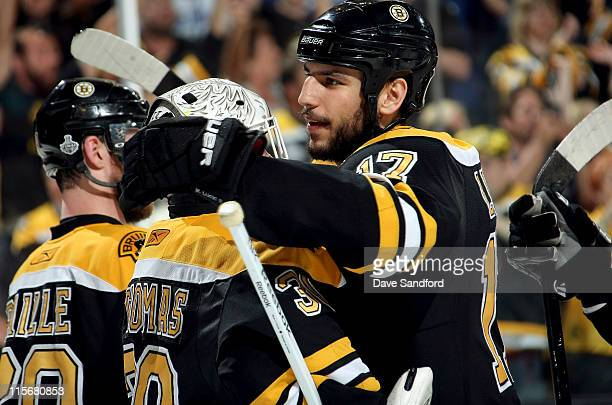 Milan Lucic of the Boston Bruins congratulates goaltender Tim Thomas aftertheir 40 victory over the Vancouver Canucks in Game Four of the 2011 NHL...