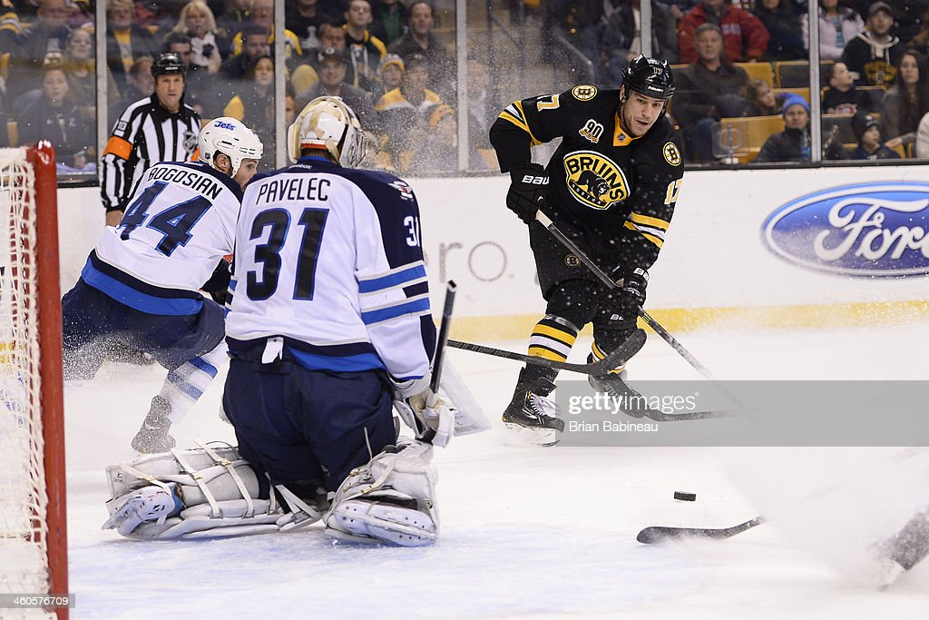 Milan Lucic #17 of the Boston Bruins passes the puck against the Winnipeg Jets at the TD Garden on January 4, 2014 in Boston, Massachusetts.
