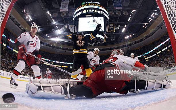 Milan Lucic of the Boston Bruins scores a goal in the third period to force overtime as Cam Ward and Rod Brind'Amour of the Carolina Hurricanes...