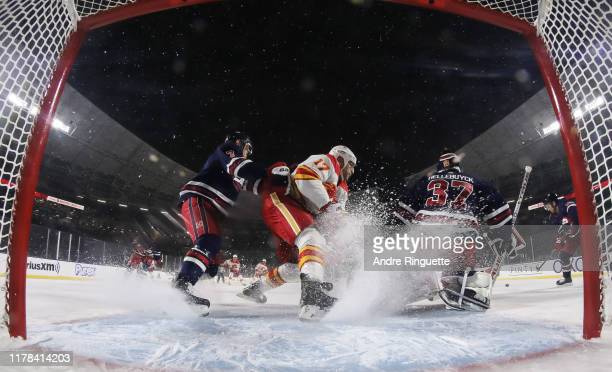 Milan Lucic of the Calgary Flames battles for position with Dmitry Kulikov of the Winnipeg Jets in front of Connor Hellebuyck during the 2019 Tim...