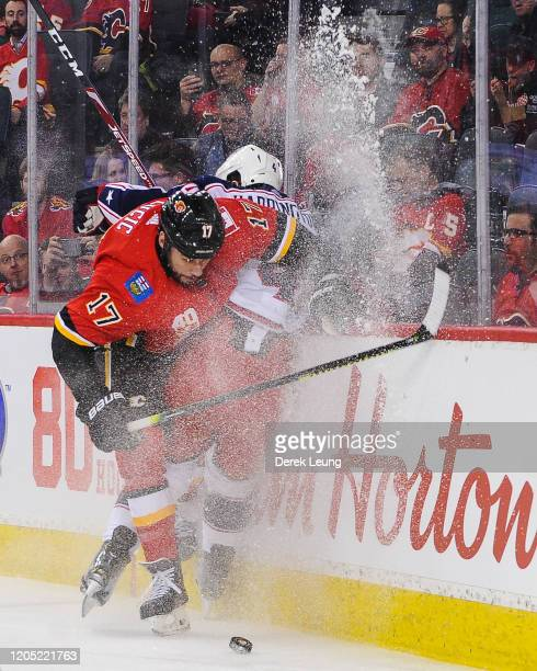 Milan Lucic of the Calgary Flames checks Scott Harrington of the Columbus Blue Jackets during an NHL game at Scotiabank Saddledome on March 4 2020 in...