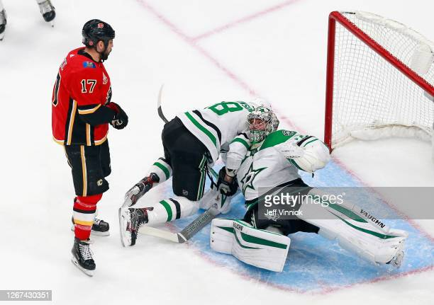 Milan Lucic of the Calgary Flames pushes Jason Dickinson of the Dallas Stars on top of Anton Khudobin of the Dallas Stars during the first period in...
