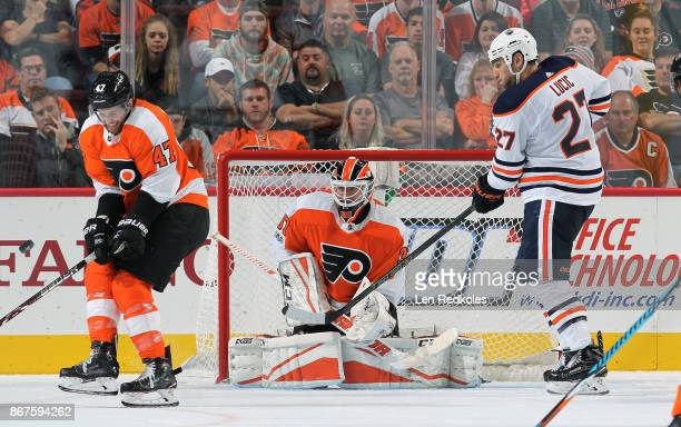 Milan Lucic of the Edmonton Oilers attempts to deflect a shot on goal against Andrew MacDonald and Brian Elliott of the Philadelphia Flyers on...