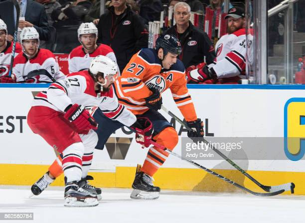 Milan Lucic of the Edmonton Oilers battles against Justin Faulk of the Carolina Hurricanes on October 17 2017 at Rogers Place in Edmonton Alberta...