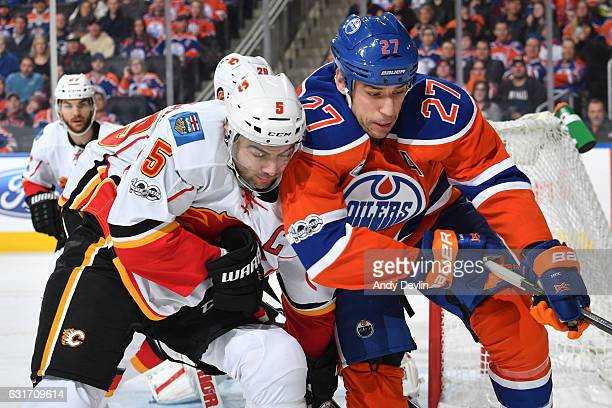 Milan Lucic of the Edmonton Oilers battles for the puck against Mark Giordano of the Calgary Flames on January 14 2017 at Rogers Place in Edmonton...