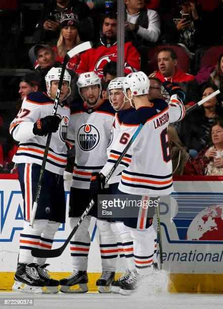 Milan Lucic of the Edmonton Oilers is congratulated by teammates Anton Slepyshev and Adam Larsson after Lucic scored in the second period against the...