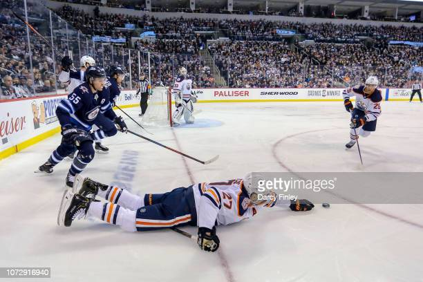 Milan Lucic of the Edmonton Oilers reaches for the loose puck after falling to the ice during second period action against the Winnipeg Jets at the...