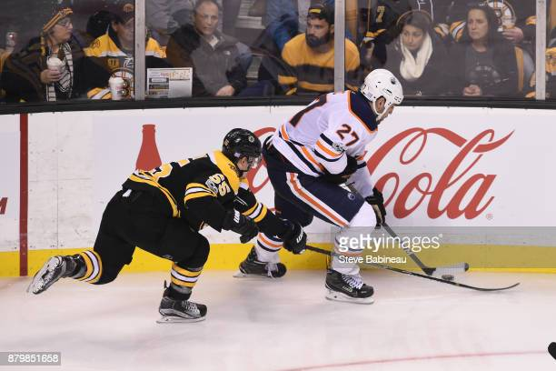Milan Lucic of the Edmonton Oilers skates with the puck against Noel Acciari of the Boston Bruins at the TD Garden on November 26 2017 in Boston...