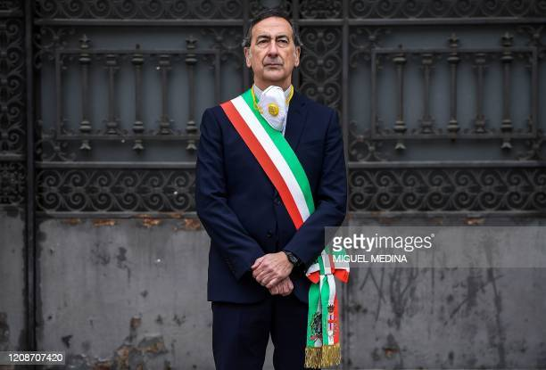 Milan mayor Giuseppe Sala stands at attention outside the city hall during a minute of silence at noon on March 31, 2020 in Milan as flags are being...