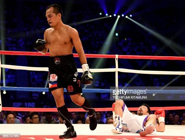 Milan Melindo of Philippines celebrates beside Akira Yaegashi of Japan after winning their IBF junior flyweight title boxing bout in Tokyo on May 21,...