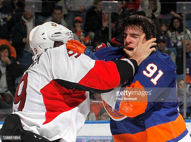 Milan Michalek of the Ottawa Senators fights with John Tavares of the New York Islanders during the second period of an NHL hockey game at the Nassau...