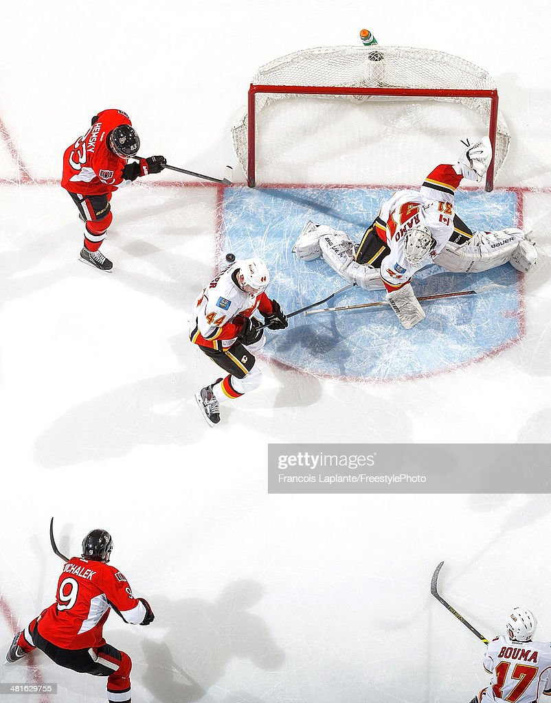 Milan Michalek #9 of the Ottawa Senators scores a goal as Ales Hemsky #83 takes position against Chris Butler #44 and Karri Ramo #31 of the Calgary Flames during an NHL game at Canadian Tire Centre on March 30, 2014 in Ottawa, Ontario, Canada.