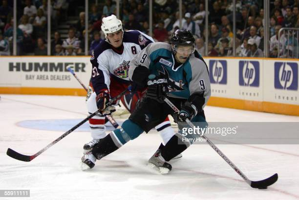 Milan Michalek of the San Jose Sharks moves the puck against defenseman Adam Foote of the Columbus Blue Jackets during the second period of the...