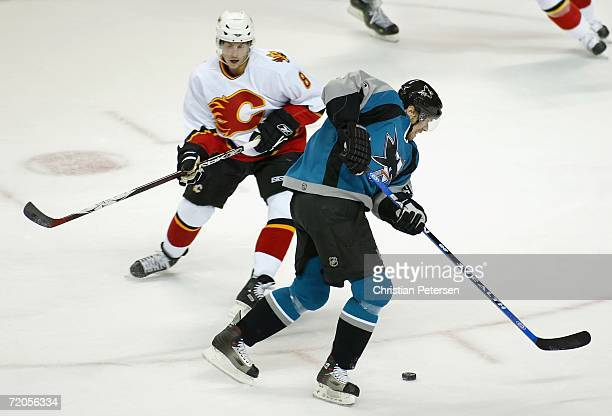 Milan Michalek of the San Jose Sharks skates past Brad Ference of the Calgary Flames on his way to score a goal during the first period of the...