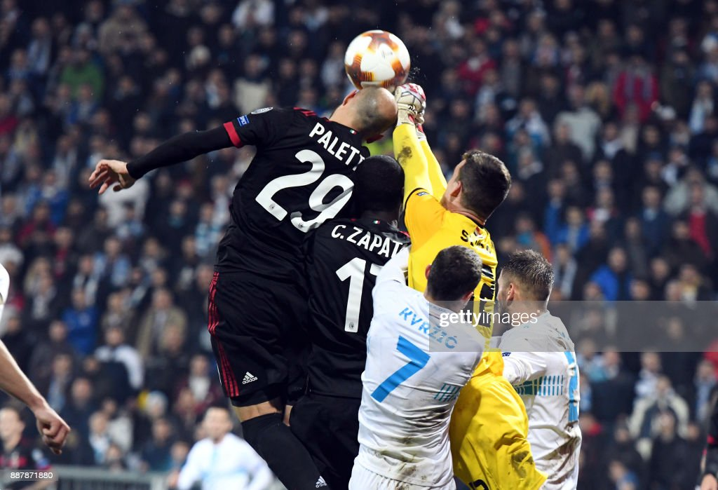 AC Milan midfielders Gabriel Paletta (L) and Cristian Zapatta (C) jump for the ball with Rijeka's goalkepper Simon Sluga (yellow jersey) during the UEFA Europa League Group D football match between HNK Rijeka and AC Milan at the Rujevica Stadium in Rijeka on December 07, 2017. /