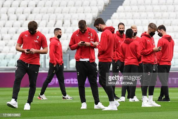 Milan players check their smartphone as they gather on the pitch prior to the Italian Cup semi-final second leg football match Juventus vs AC Milan...