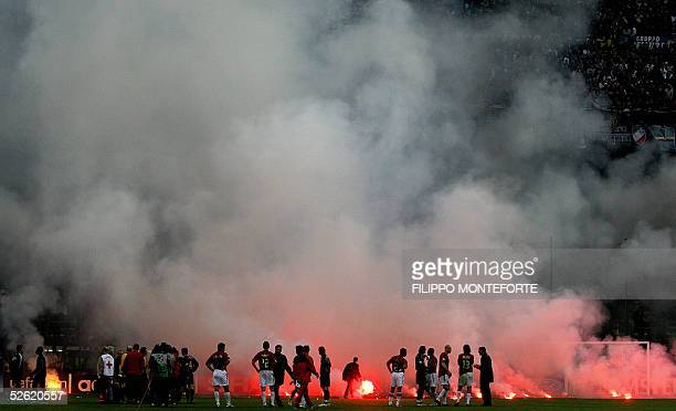 Milan players wait for the smoke to disappear after InterMilan's fans throw fireworks on the field during the quarter final second leg football match...