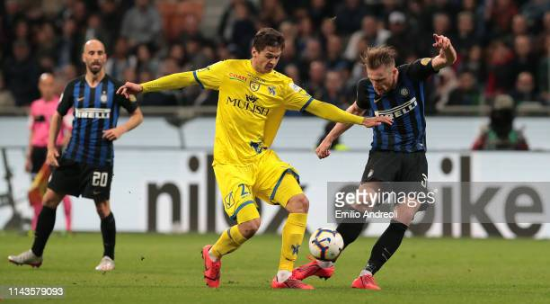 Milan Skriniar of FC Internazionale is challenged by Sergej Grubac of Chievo Verona during the Serie A match between FC Internazionale and Chievo at...
