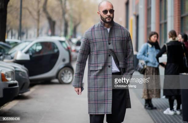Milan Vukmirovic wearing checked grey wool coat is seen outside Fendi during Milan Men's Fashion Week Fall/Winter 2018/19 on January 15 2018 in Milan...