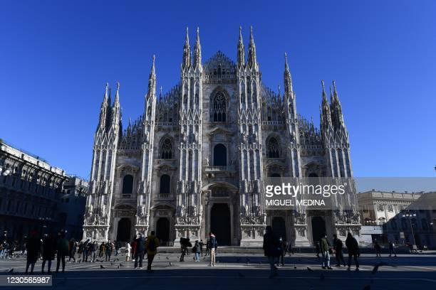 Milanese wearing protective masks enjoy the nice weather in front of the Duomo di Milano on Piazza del Duomo in central Milan on January 13, 2021. -...