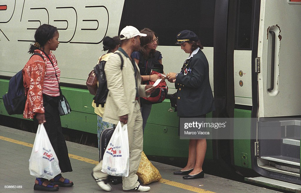 passengers about to enter an high speed train ask for direction to the train conductor