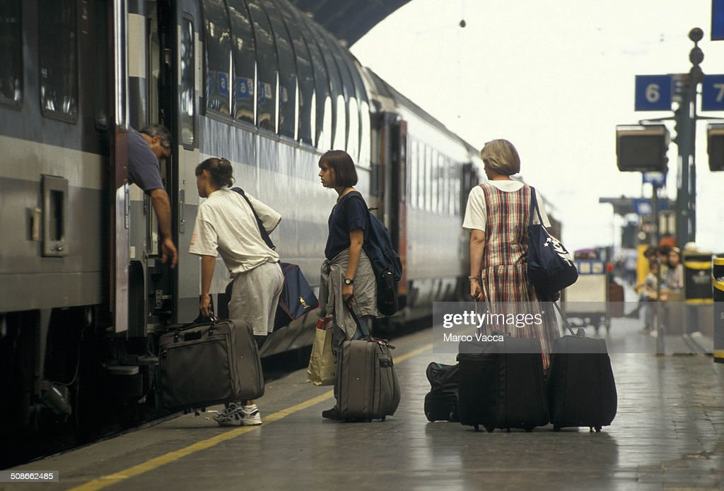 passengers loaded with luggage in line to enter a railroad car