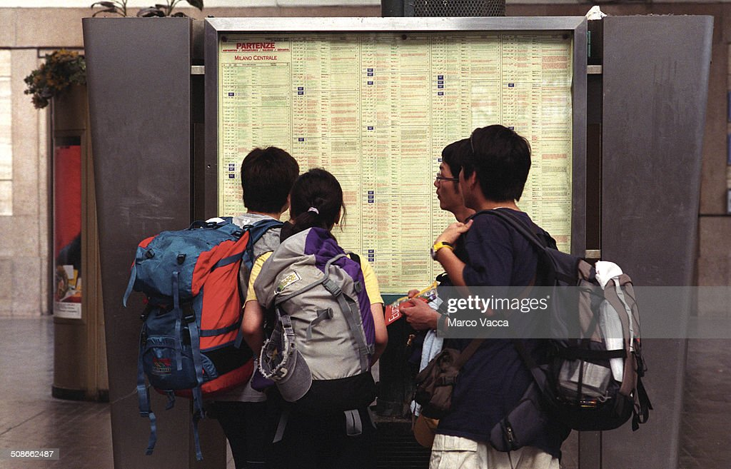 Milano Italy, young Japanese backpackers consulting a time table in the central station